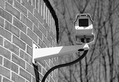 Security camera attached to the outside of a building's brick wall