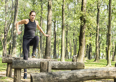 Female jumping across wooden barriers outdoors