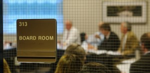"Close up of ""Board Room"" sign on window into the MCIT Board room while blurred image of board members appears in background during board meetings"