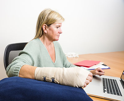 A female telecommuter at her desk with an elevated wrist to relieve the pain and swelling of a sprain.
