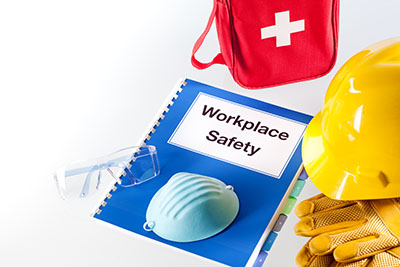 Still life of a handbook manual for workplace safety and various safety equipment.
