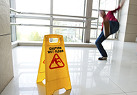 "Man Slipping on Floor with sign stating ""caution wet floor"" in foreground"
