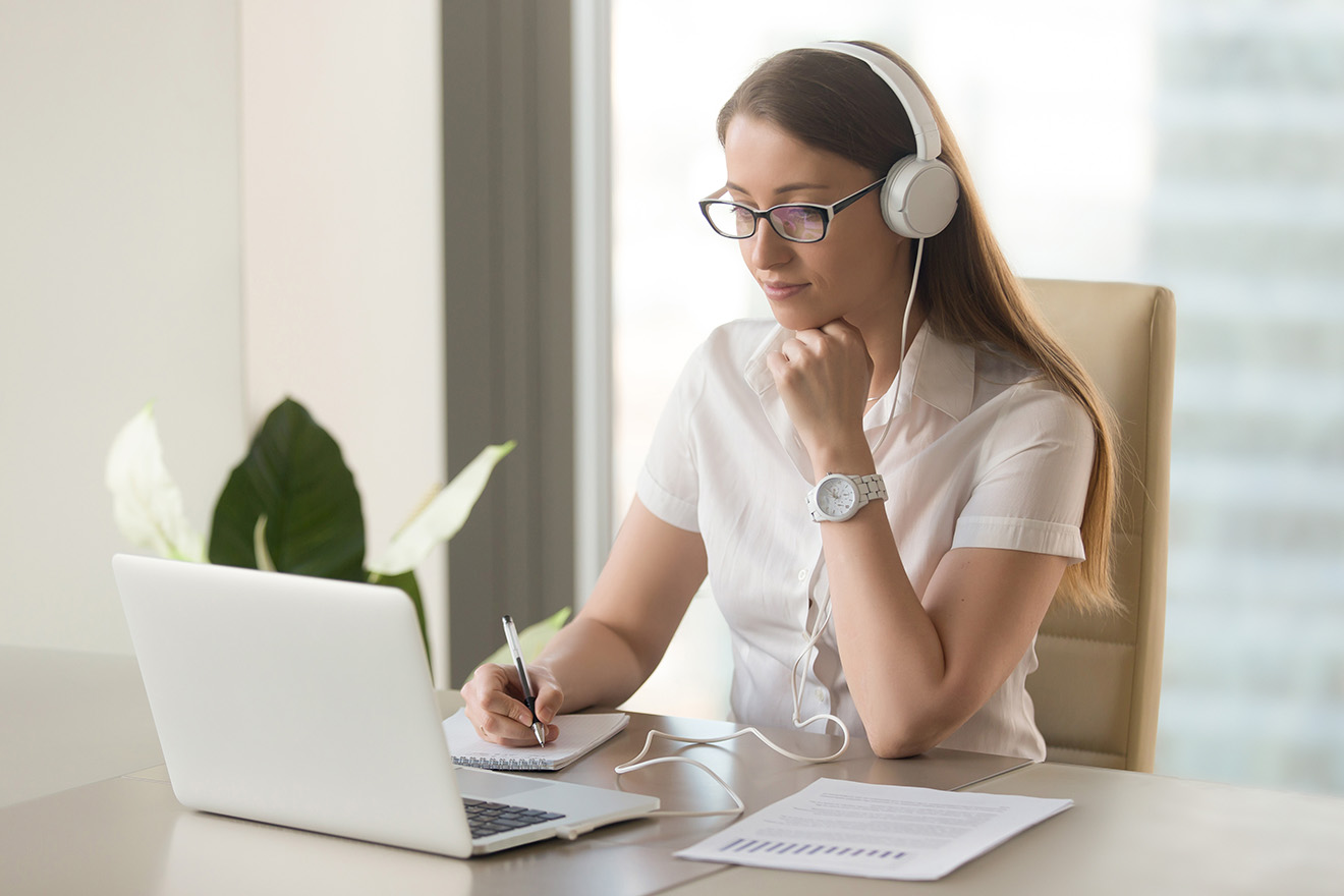 Woman with headphones on looks at computer screen while sitting at her desk with pen in hand taking notes
