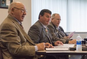 Three MCIT board members listen to a report during a board meeting