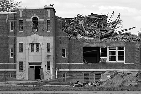 Public building after tornado damage; roof collapsed and windows broken