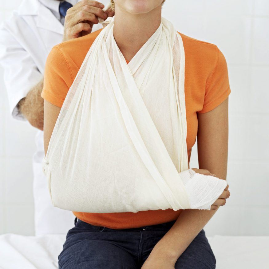 Woman with arm wrapped in bandage and in a sling being examined by a medical provider.
