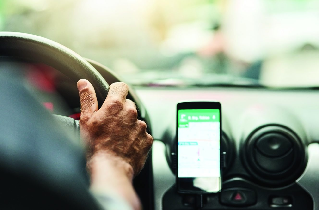 Closeup shot of a man using a phone to find directions while driving, hands-free cellphone dock used