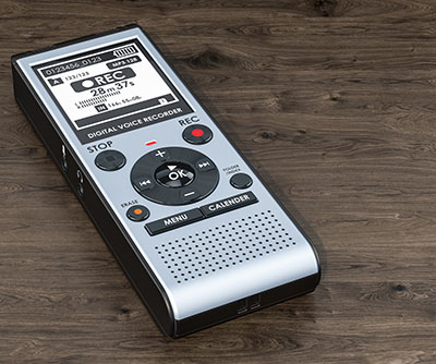 Digital voice recorder, dictaphone on the wooden table.