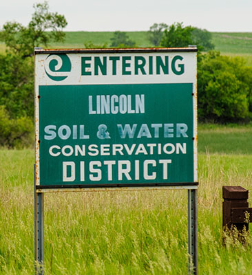 """Roadside sign says, """"Entering Lincoln County Soil and Water Conservation District"""" placed in tall grass prairie"""