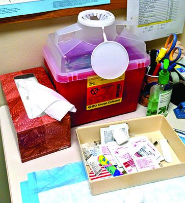 used sharps safety receptacle on desk to reduce exposure to blood borne  pathogens
