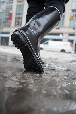 Close-up of a woman's boots walking through slush ice and snow