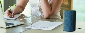 Close up of person working at laptop and a personal digital assistant speaker is set on the corner of the desk