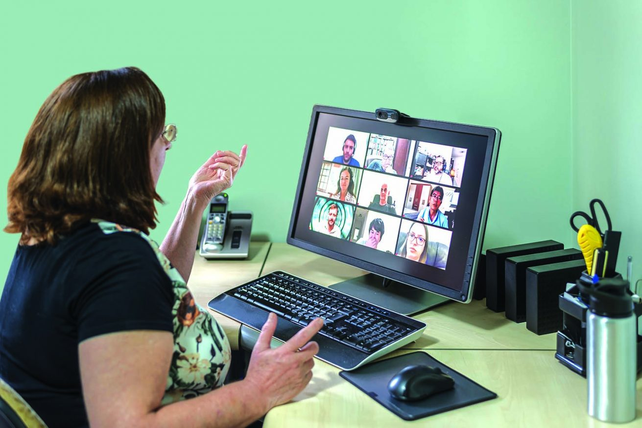 Woman attending a video conference meeting on her desktop computer