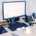 Office desk with PC equipment, stationary, landline phone and mobile phone