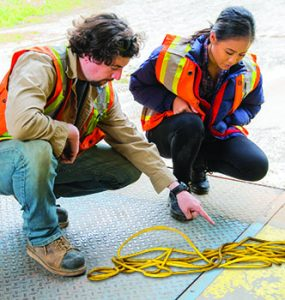 One employee explains to another the danger of leaving twisted power cords in walkways.