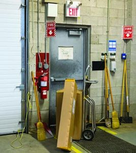 A blocked fire exit door in an industrial building in violation of safety regulations