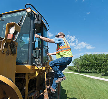 highway employee climbs into large equipment using three points of contact