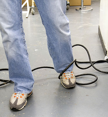 Man's foot is caught up in electrical power cord strung across the walkway, creating a tripping hazard