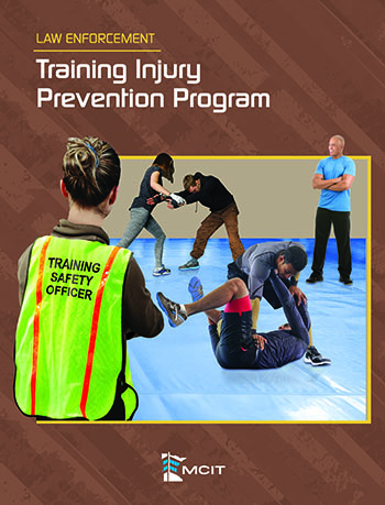 """Cover image of """"Law Enforcement Training Injury Prevention Program"""" guide book. Shows back of woman looking into an active training session while she wears a vest marked """"training safety officer"""""""