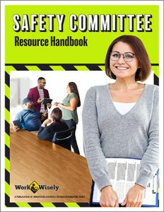 """Cover of """"Safety Committee Resource Handbook"""" showing woman holding clipboard with committee members meeting in the background"""