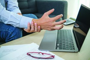 Man working from home with laptop feeling wrist pain